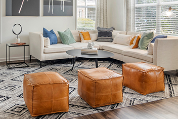 Tan and white living area with sectional and orange leather ottomans