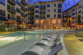 Lounge chairs line a luxury apartment pool at dusk